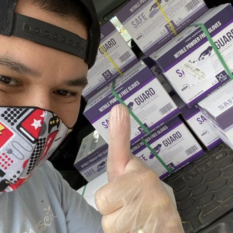 Owner Sal Reina takes a selfie in front of the the glove boxes that he will be donating to local hospitals.