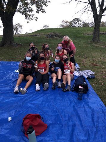 After an arduous meet with skilled competition, the varsity cross country girls team pose for a quick picture with their medals after they earn the title of League Champions.