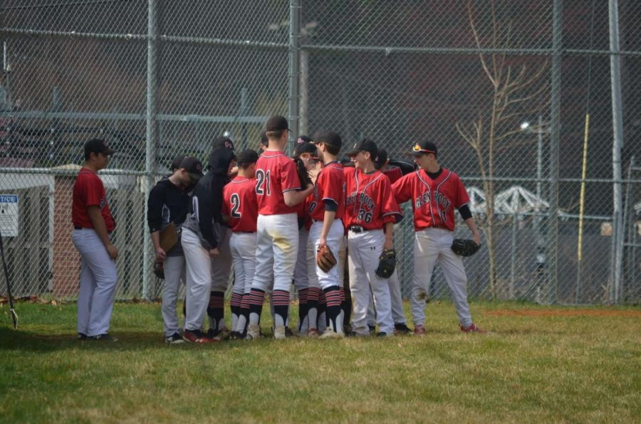 The Glen Rock High School Varsity Baseball team gathers in a huddle before they take the field.